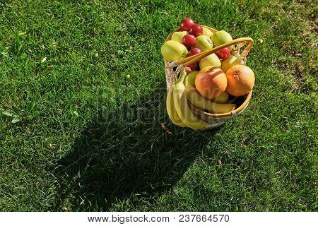 Picnic Basket On Grass Background. Fresh Fruits Top View. Summer Dieting Plans.
