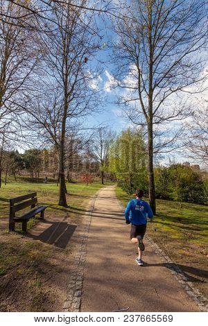 Vila Nova de Famalicao, Portugal - March 31, 2018: Mature man running or jogging in Parque da Devesa Urban Park. Built near the center of the city.