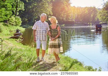 Happy Senior Couple Near Water. Old People Smiling, Summer Nature.