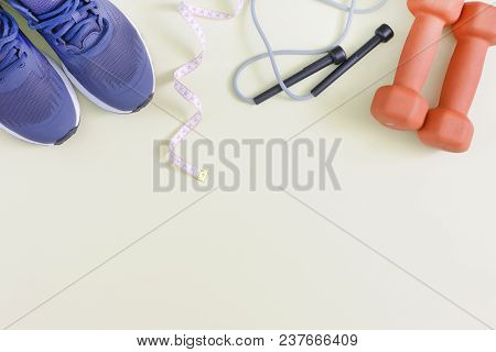 Fitness Background With Place For Text. Blue Sneakers, Dumbbells, Skipping Rope And Tape Measure. Mo