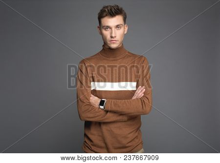 Innovation Concept. Waist Up Portrait Of Solemn Young Man Posing With Crossed Hands. Smartwatch Is O