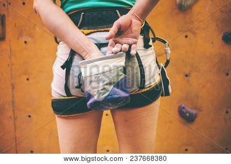 The Climber Is Preparing To Climb The Route. The Woman Rubs Her Hands With Magnesium. Preparation Fo