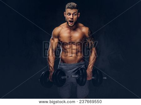 Funny Stylish Bodybuilder With A Tattoo On His Arm, Doing The Exercises With Dumbbells. Isolated On
