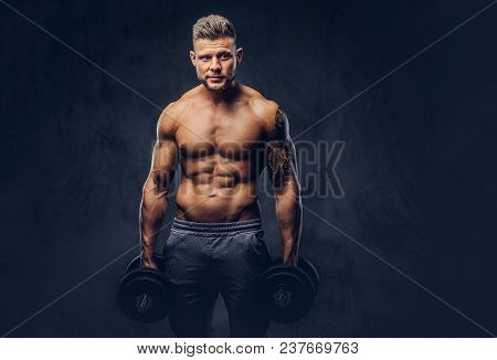 Powerful Stylish Bodybuilder With Tattoo On His Arm, Posing With Dumbbells In A Studio, Looking At T