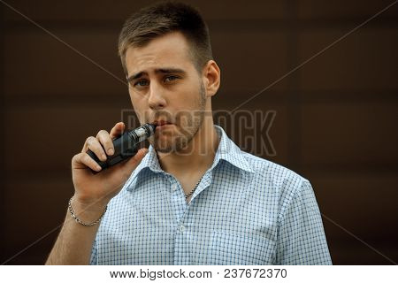 Vape Man. Portrait Of A Handsome Young White Guy With Modern Haircut In In Checkered Sleeveless Shir