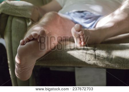 Close Up Of The Bare Feet And Legs Of A Middle Aged Man Who Sits And Rests Them On A Reclining Chair