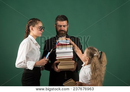 Teacher Man And Girls Hold Book Pile At School. School Time Of Sisters And Father In Library. Educat