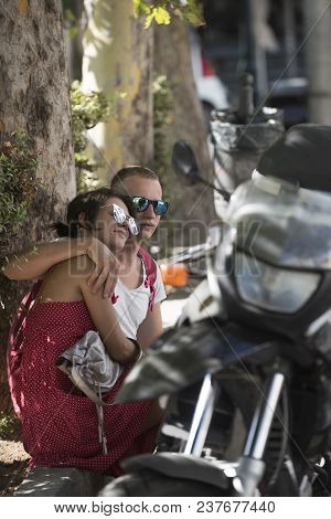 Couple In Love Sit In Shadow Of Trees On Hot Summer Day Near Parked Motorbike, Defocused. Refreshmen