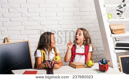 School Time Of Girls. Little Girls Eat Apple At Lunch Break. Happy School Kids At Lesson In Septembe