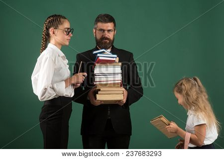 Back To School And Home Schooling. Teacher Man And Girls Hold Book Pile At School. Literature Lesson