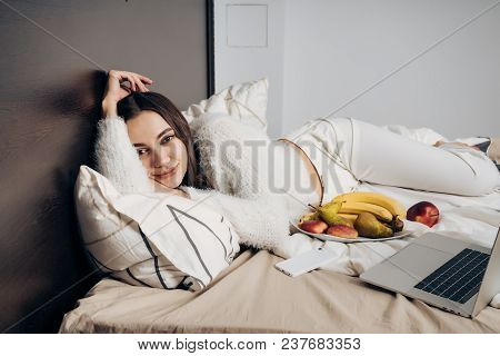 Beautiful Young Girl Lies On A Bed, Relaxes And Relaxes, Eats Fruit And Looks At A Film On A Laptop