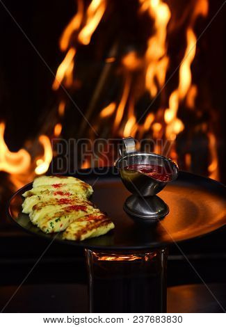 Delicious Cheesy Dish Served In Restaurant On Black Dishes. Dish Of Grilled Cheese Served With Raspb