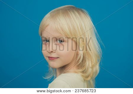 Fashion Style And Beauty Look. Fashion Hairstyle Of Cute Little Blond Girl On Blue Background