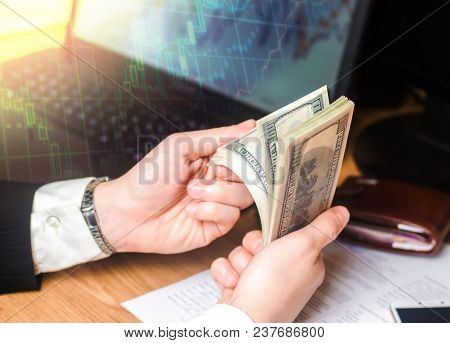 A businessman in a suit counts dollars at a table in the hands of a laptop and financial charts. A concept of a successful business, successful selling, savings, investment. Playing on the exchange