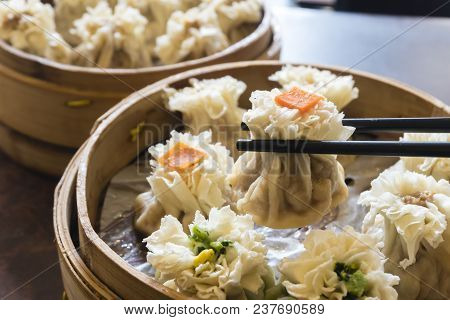 Enjoying Traditional Chinese Dumpling Called Shumai At A Restaurant