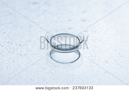 Contact Lens With Water Drops On A Mirror Background.