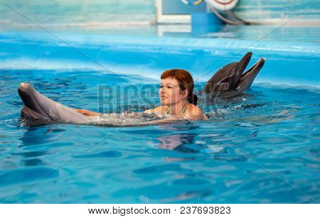 Young Happy Girl Playing With Dolphin In Swimming Pool