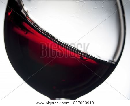 Red Wine In Wineglass On A Grey Background. Abstract Splashing. Closeup.