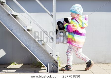 Little Girl Is Playing With Plush Toys Near Metal Staircase On Bright Sunny Afternoon.