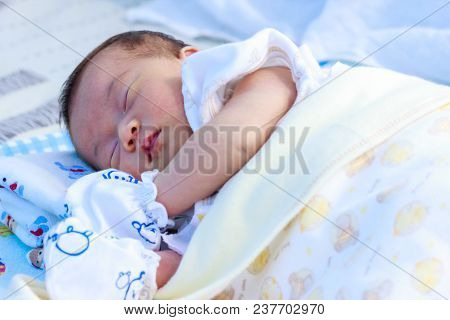 Closeup Portrait Of A One Month Old New Born Girl Resting Peacefully In The Morning. Charming Baby C
