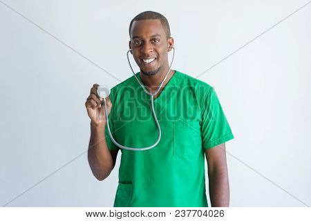 Portrait Of Cheerful Young Doctor Listening With Stethoscope. African American Cardiologist Wearing