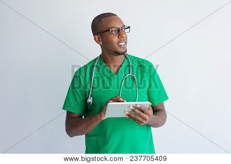 Smiling African American Doctor Using Digital Tablet. Portrait Of Young Physician Wearing Green Scru