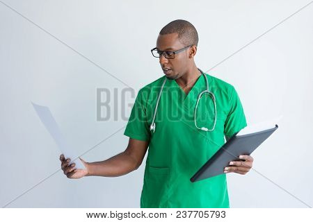Young Doctor Looking At Medical Test Results. Portrait Of African American Physician Wearing Glasses
