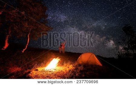 Camping Fire And Orange Tent Under The Amazing Starry Sky With A Lot Of Shining Stars. Man Shows The