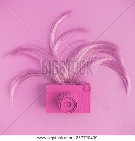 Retro Camera And Female Hair Flat Lay In Pastel Pink Color. Minimal Fashion Creative Concept.