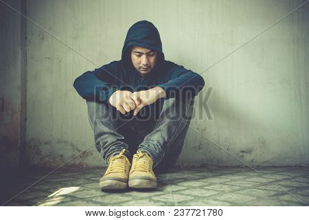 Young Man In Hood Sitting In Room Corner. Guy Feeling Sad And Lonely.