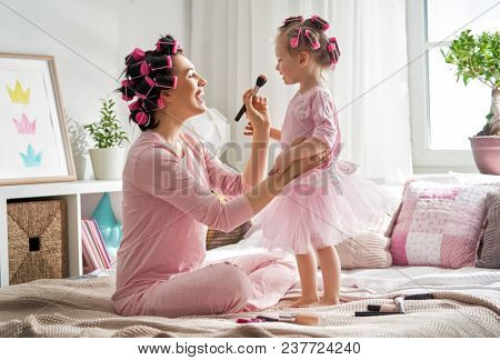 Happy loving family. Mother and daughter are doing hair and having fun. Mom and her child girl playing, kissing and hugging.