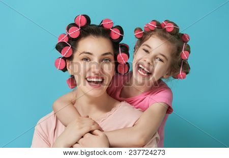 Happy loving family. Mother and daughter are doing hair and having fun. Mom and her child girl playing and hugging.