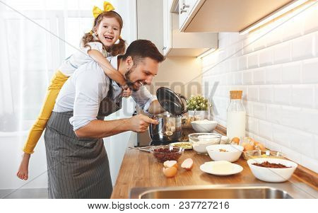 Happy Family In Kitchen. Father And Child Daughter Knead Dough And Bake The Biscuits Together