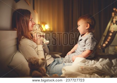 Mother Puts The Baby Son To Sleep In Evening In Bed In Dark