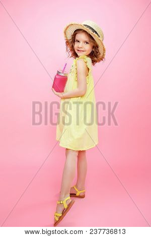 Stylish Little Girl In Yellow Dress And Straw Hat Posing With Glass Of Pink Lemonade.