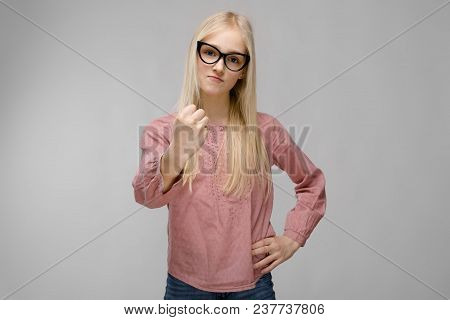 Cute Naive Sweet Caucasian Young Teen Girl Looking In Camera Standing In Studio In Glasses Show Sign