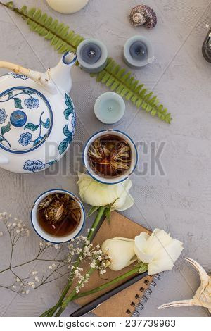 Top View Shot Of Herbal Tea, Rose Flowers And Candles On Concrete Tabletop.