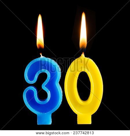 Burning Birthday Candles In The Form Of 30 Thirty Figures For Cake Isolated On Black Background. The