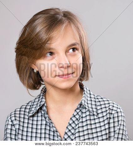 Beautiful Caucasian Teen Girl On Gray Background. Schoolgirl Looking Away. Funny Cute Teenager Child