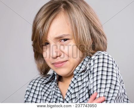 Beautiful Caucasian Teen Girl On Gray Background. Schoolgirl Looking At Camera. Funny Cute Teenager