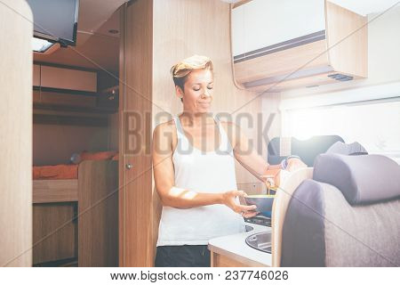 Young Woman Preparing The Meal In A Caravan Kitchen On A Holiday Adventure Trip. Interior View