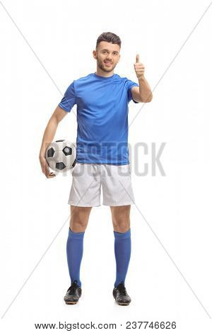 Full length portrait of a soccer player holding a football and making a thumb up sign isolated on white background