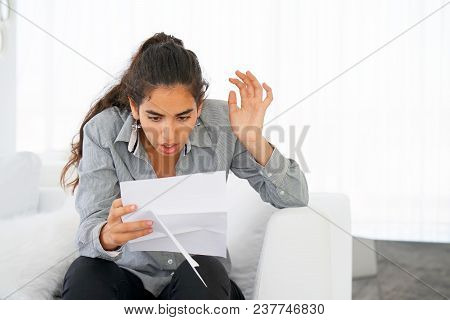 Woman Reads Negative News In A Letter At Home On The Couch. The Shaken Business Manager Of The Beaut