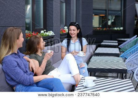 Smiling Female Friends Laughing At Cafe And Gossiping Drinking Coffee. Concept Of Friendship And Cha