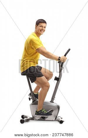 Young man cycling on a stationary bike and looking at the camera isolated on white background poster