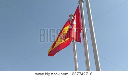 Flags Of Spain And The Community Of Madrid Waving. Mast Seen From Below