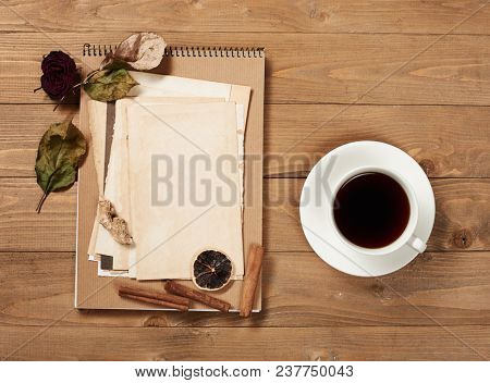 Cup of coffee and cookies with old sheet of paper on wooden background, spice and decoration, top view, retro style