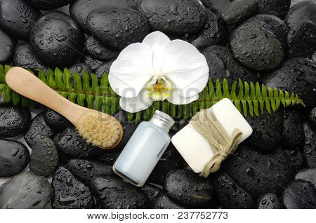 Wet black stones background with white orchid,soap,brush ,fern on wet background