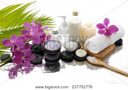 Spa still life with black stones and orchid, candle, salt in bowl ,roller on bowl, bottle, oil