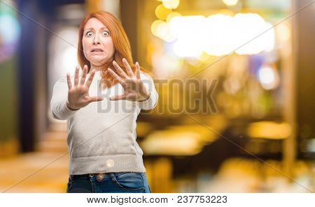 Beautiful young redhead woman disgusted and angry, keeping hands in stop gesture, as a defense, shouting at night